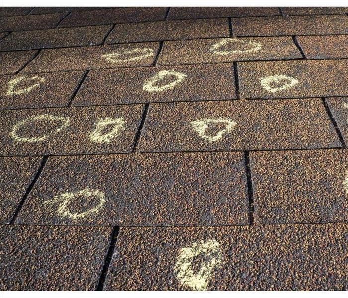Insurance adjuster marked the hail damage on a insured's roof.