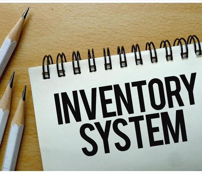 Inventory System text written on a notebook with pencils